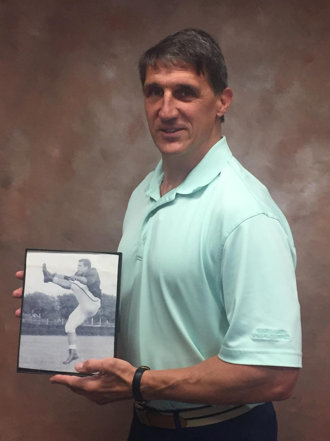 Mr. Michaels poses holding up a picture of his father, Lou Michaels.